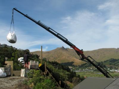 Crane lifting a full bag onto a hillside site