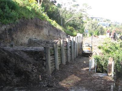 Timber half-round hillside retaining wall under contruction